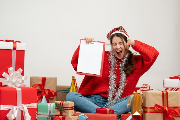 Вид спереди приподнятая девушка в шляпе санта-клауса с файлами, сидящими вокруг подарков