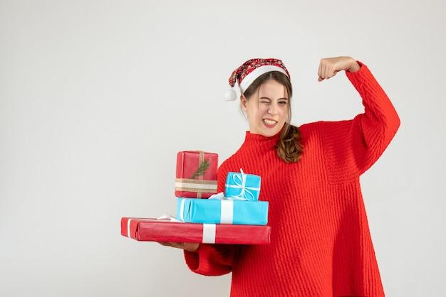 Ragazza euforica di vista frontale con il cappello della santa che tiene i suoi regali di natale che mostrano il muscolo