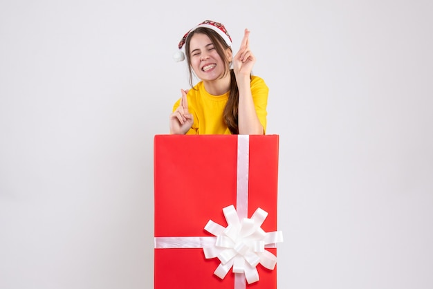 Front view elated girl with santa hat making good luck sign standing behind big xmas gift
