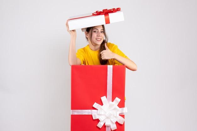 큰 크리스마스 선물 뒤에 서 가입 엄지 손가락을 만드는 산타 모자와 전면보기 의기 양양 소녀