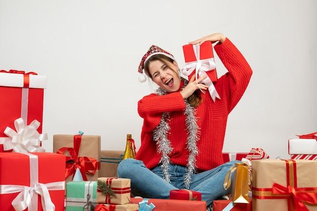 プレゼントの周りに座っている彼女の首に贈り物を上げるサンタの帽子をかぶった正面図の高揚した女の子