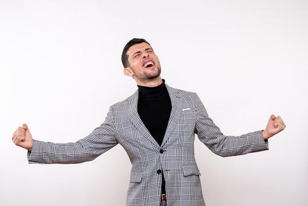 Вид спереди восторженный красивый мужчина в костюме, демонстрирующий выигрышный жест, стоящий на белом фоне