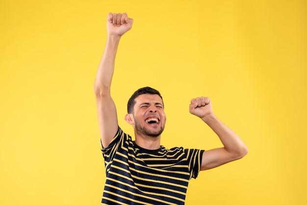 Vista frontale euforico uomo bello in bianco e nero a strisce t-shirt giallo sfondo isolato
