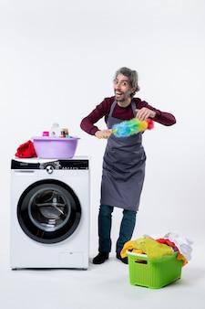 흰색 배경에 세탁기 근처에 서 있는 살포기를 들고 의기양양한 가정부 남자 전면 보기