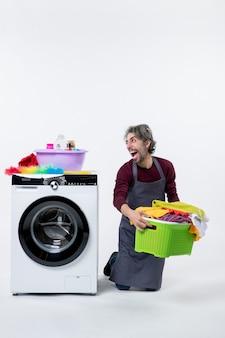 正面図白い背景の上の洗濯かごを保持している膝の上に立っている家政婦の男を高揚