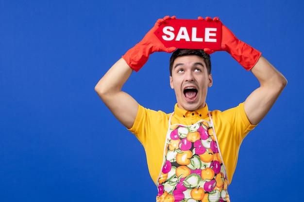 正面図は青いスペースで彼の頭の上に販売サインを上げる黄色のtシャツで男性の家政婦を高揚させた