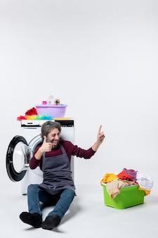 正面図は、白い背景の上の洗濯機の洗濯かごの前に座って親指を立てるサインを作る男性の家政婦を高揚させた