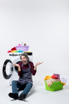 Vista frontale euforico governante maschio seduto di fronte alla lavatrice aprendo le mani cesto della biancheria su sfondo bianco