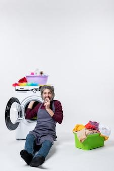 正面図は、白い孤立した背景に洗濯機の緑の洗濯かごの前に座っている男性の家政婦を大喜び