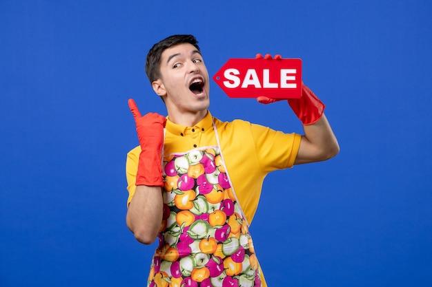 Vista frontale della governante maschio euforico con guanti di scarico rossi che tengono segno di vendita sulla parete blu