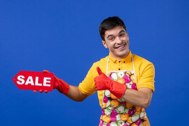 Vista frontale euforico governante maschio in maglietta gialla con cartello di vendita che fa il pollice in alto segno su spazio blu