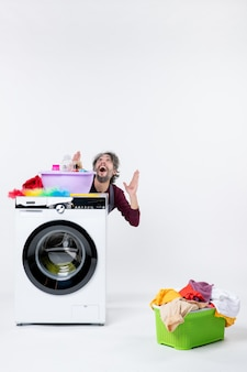 Front view elated man in apron sitting behind washer laundry basket on white background