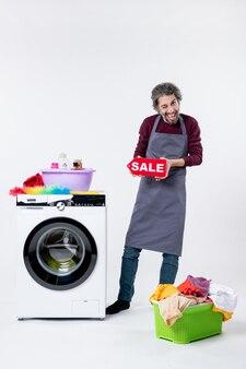 Вид спереди приподнятый мужчина в фартуке, держащий знак продажи, стоящий возле корзины для белья стиральной машины на белом фоне