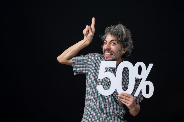 Front view elated man pointing finger up holding up mark on dark wall