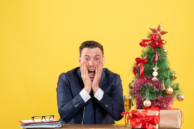 Front view of elated man putting hands on his cheek sitting at the table near xmas tree and presents on yellow