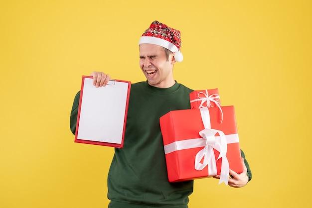Vista frontale uomo euforico con maglione verde che tiene grande regalo e appunti in piedi sul giallo