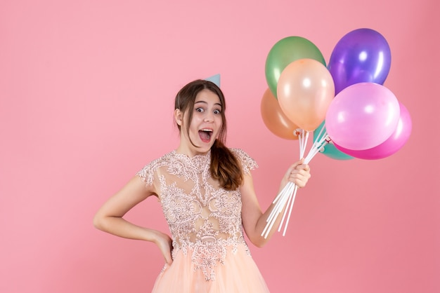 Front view elated party girl with party cap holding balloons putting hand