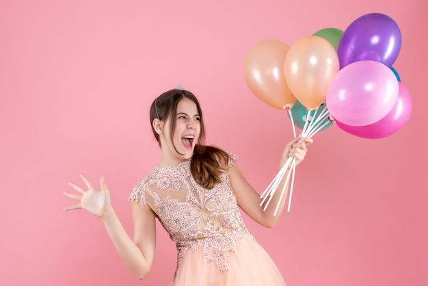 風船を保持しているパーティーキャップを持つ正面図高揚パーティーの女の子