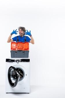 Riparatore euforico di vista frontale che apre la sua lavatrice delle mani su spazio bianco