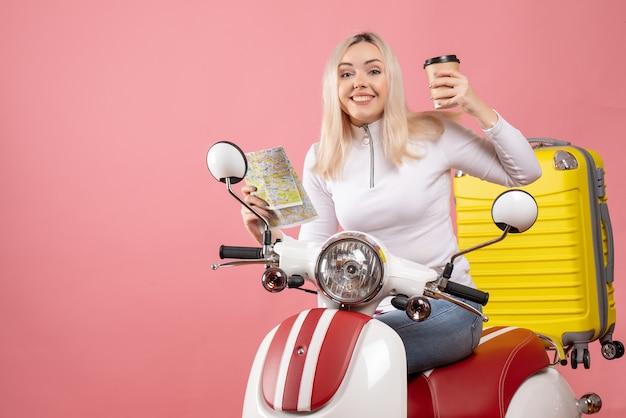 Vista frontale euforico giovane signora sul ciclomotore che tiene mappa e caffè elegante muro rosa