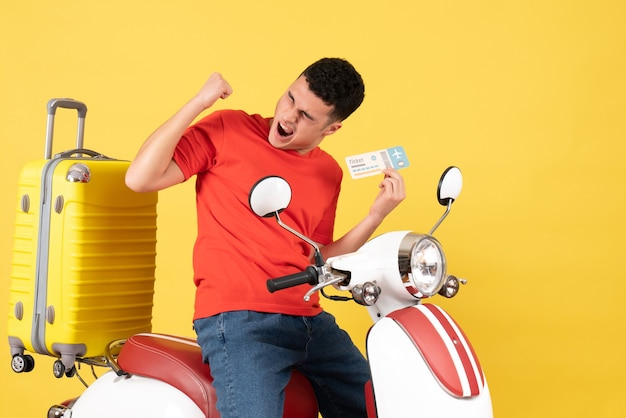 Front view elated young male in casual clothes on moped holding ticket