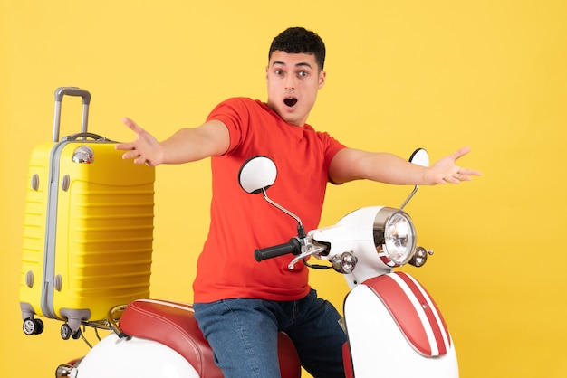 Front view elated young male in casual clothes on moped opening hands