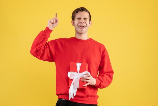 노란색에 선물을 들고 닫힌 된 눈을 가진 전면보기 의기 양양 젊은 남자