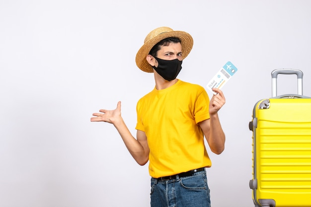 Front view elated young man with straw hat standing near yellow suitcase holding plane ticket