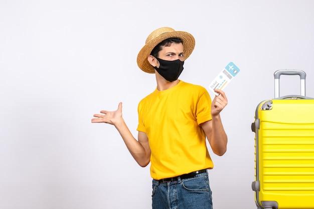正面図は飛行機のチケットを保持している黄色のスーツケースの近くに立っている麦わら帽子で若い男を高揚させた