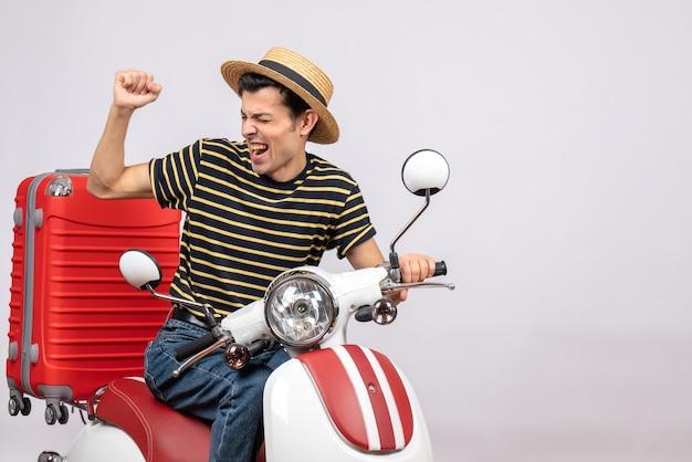 Vista frontale del giovane euforico con la valigia sul ciclomotore che esprime i suoi sentimenti