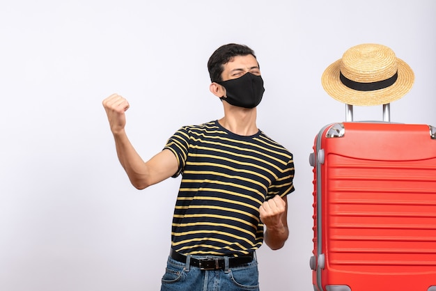 Front view elated young tourist with black mask standing near red suitcase showing his punches