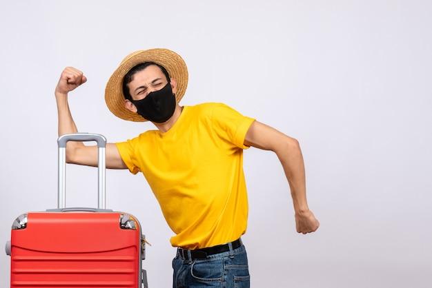 正面図黄色のtシャツと赤いスーツケースで若い観光客を大喜び