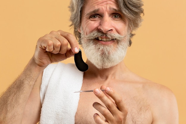 Front view of elder bearded man holding eye patches