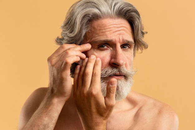 Front view of elder bearded man pointing out wrinkles