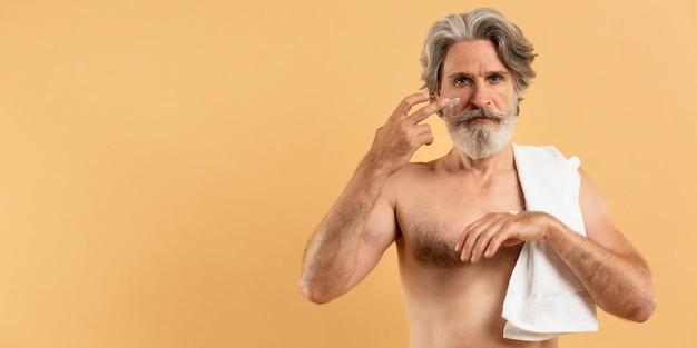 Vista frontale dell'uomo anziano barbuto con un asciugamano che applica crema