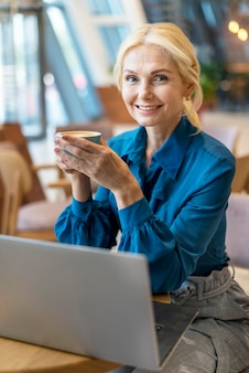 Front view of elder business woman having cup of coffee and working on laptop