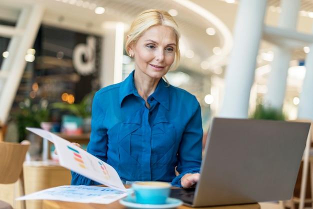 Vista frontale della donna più anziana di affari che lavora al computer portatile con caffè e documenti