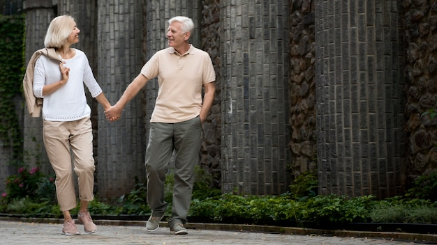 Front view of elder couple holding hands while taking a walk outdoors