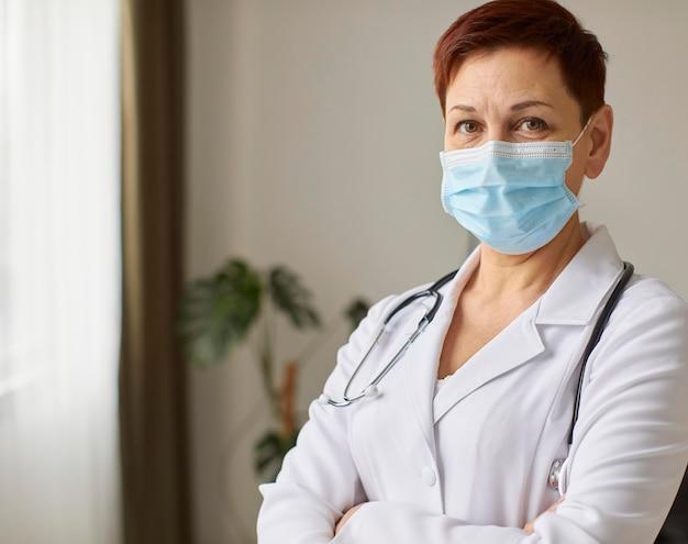 Vista frontale del medico femminile del centro di recupero covid anziano con mascherina medica