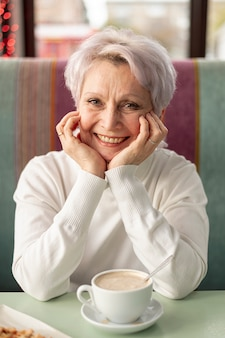 Front view elder smiley woman at restaurant