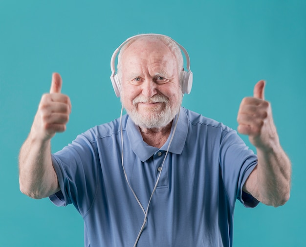 Front view elder with headphones showing ok sign