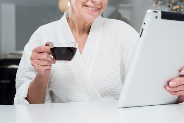 Front view of elder woman in bathrobe holding tablet and coffee cup