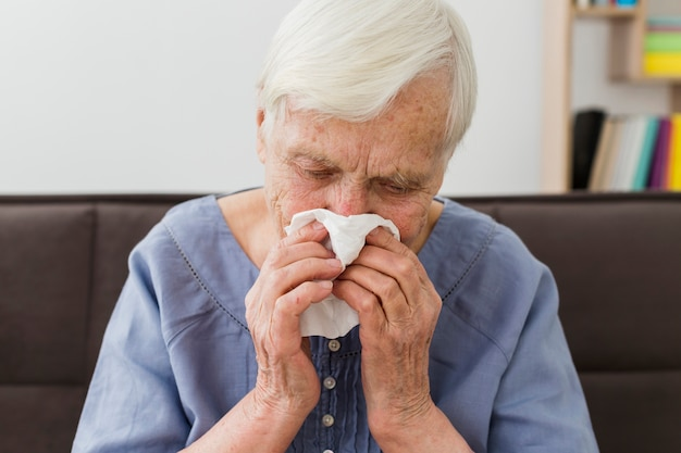Front view of elder woman blowing her nose in napkin
