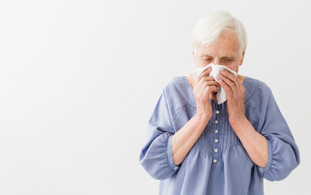 Front view of elder woman blowing her nose with copy space
