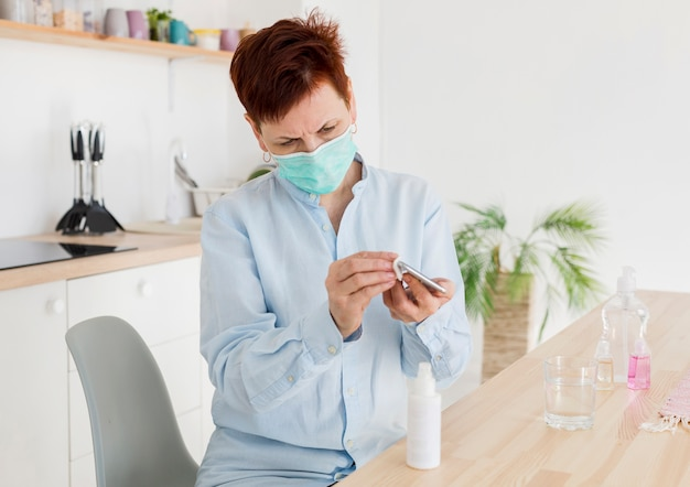 Front view of elder woman disinfecting her smartphone while wearing medical mask
