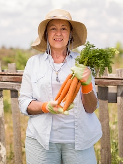 Front view elder woman holding some fresh carrots in her hand