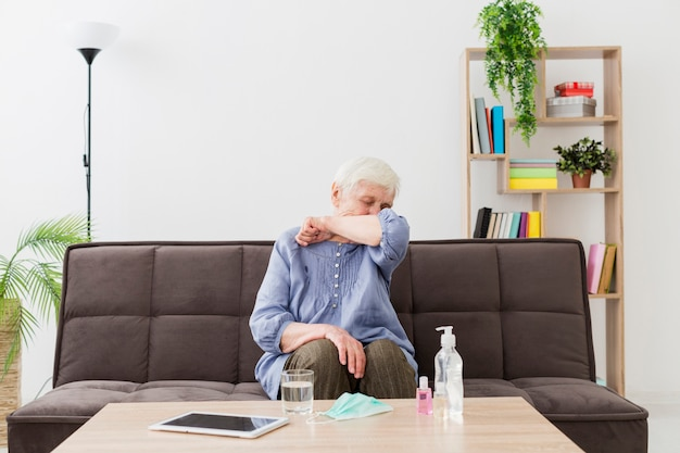 Front view of elder woman at home coughing in the elbow