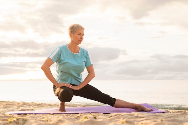 Front view of elder woman practicing yoga on beach