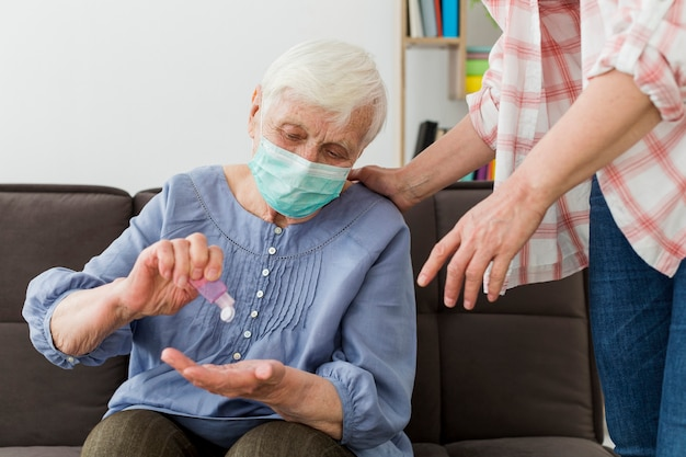Front view of elder woman using hand sanitizer while wearing medical mask