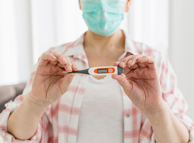 Front view of elder woman with medical mask holding up thermometer